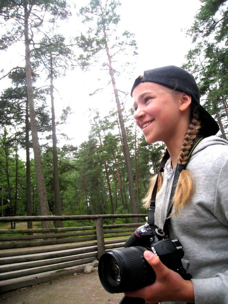 Veera Melvasalo kameran kanssa ulkona metsässä