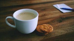 Valokuva kahvikupista, jonka vierellä kaksi pikkuleipää. Taustalla muistilappu ja kynä.